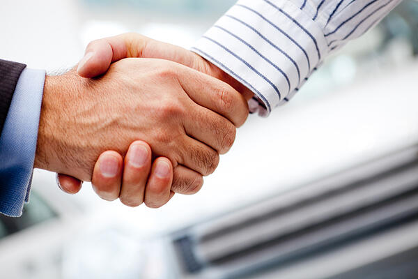 Business handshake after buying a new car